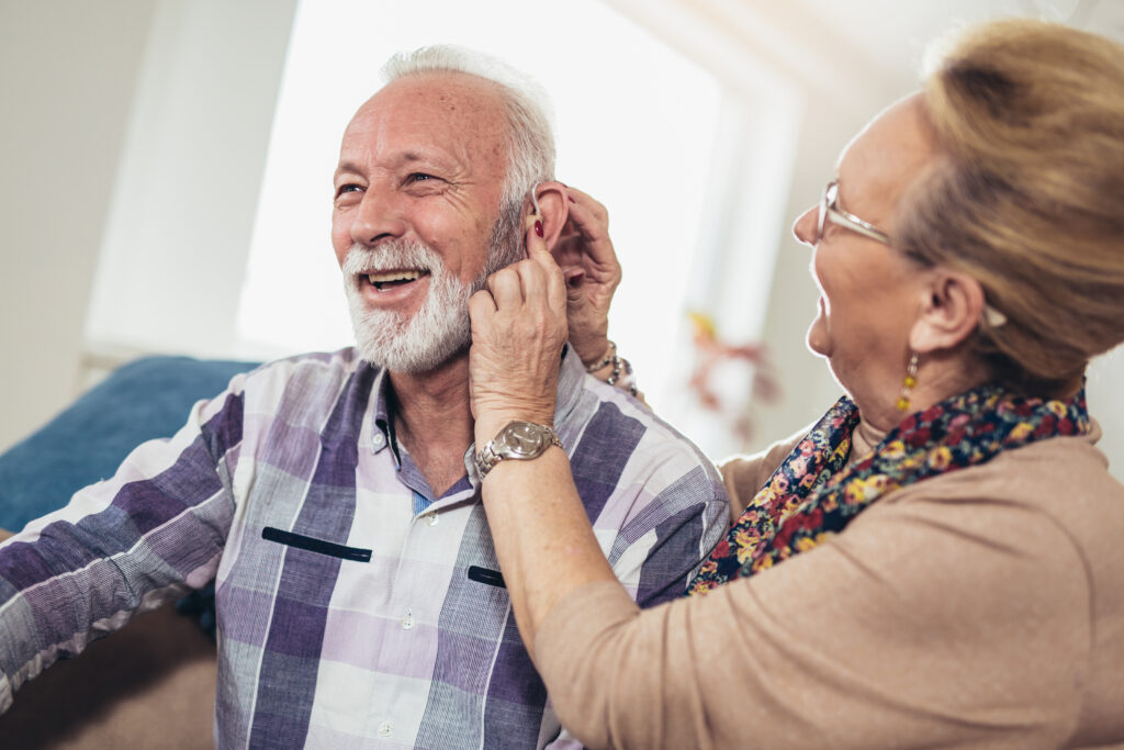 senior man wearing over the counter hearing device