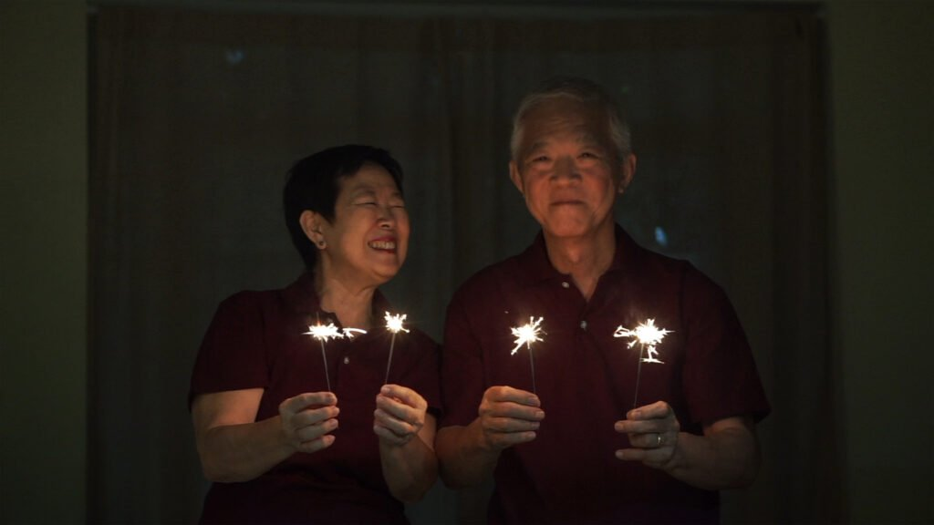 senior couple celebrating christmas in july with sparklers
