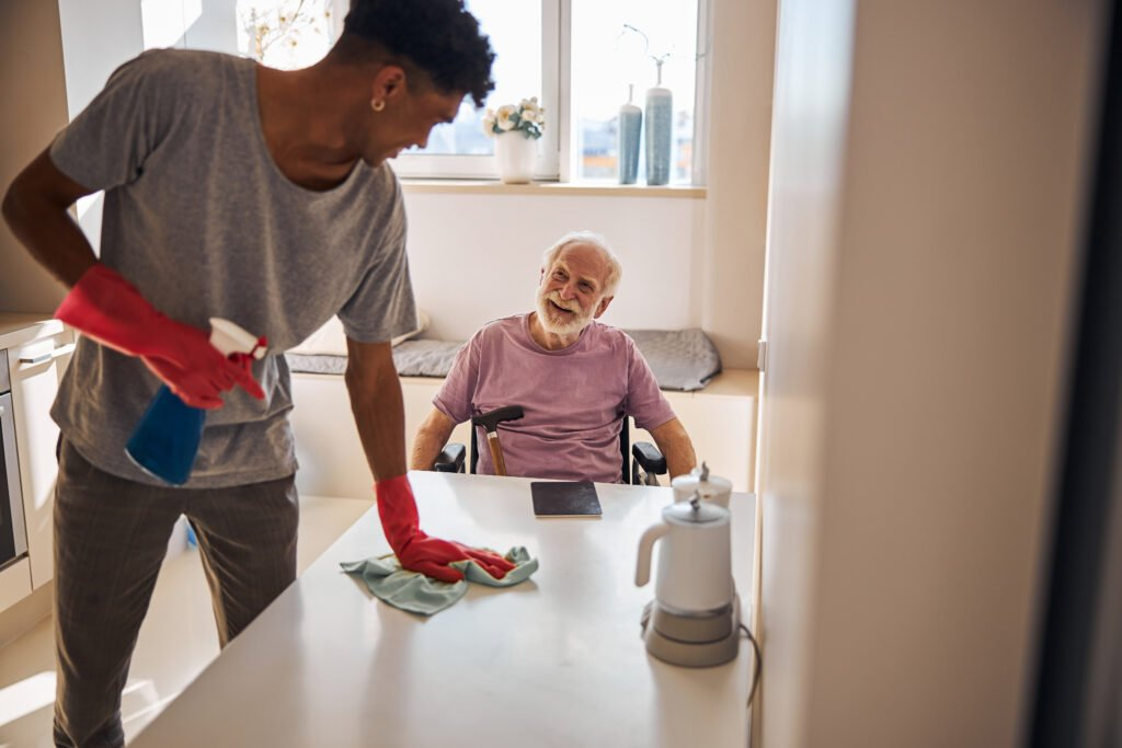 in home caregiver cleaning for senior man