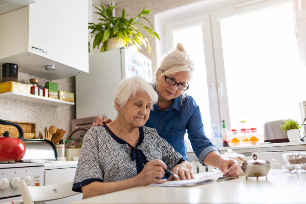 caregiver for elderly helping senior woman with finances