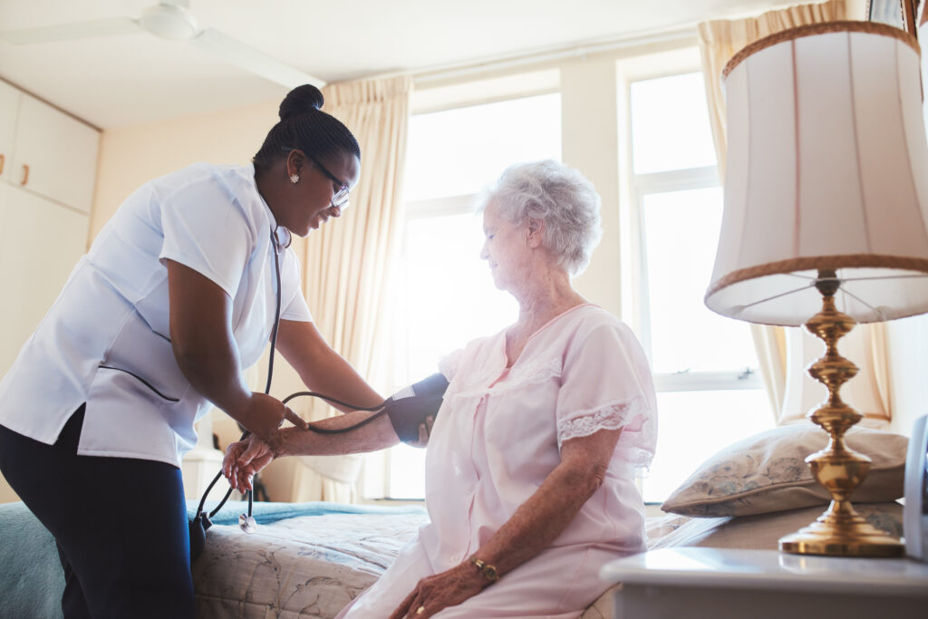 nurse helping senior woman in assisted living facility