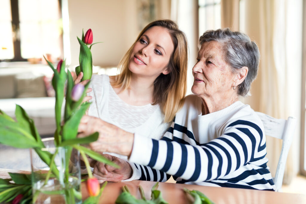 caregiver with senior and flowers