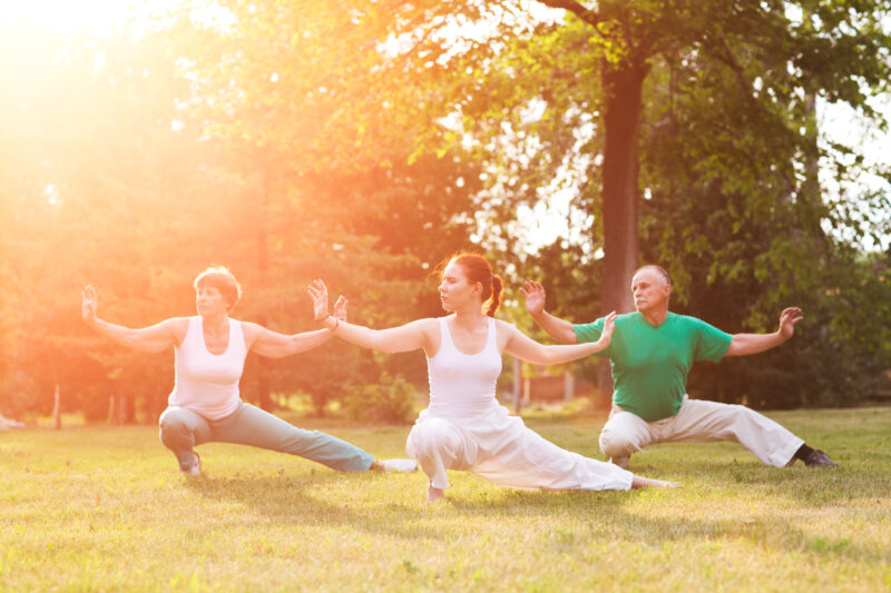 young woman practicing tai chi with seniors